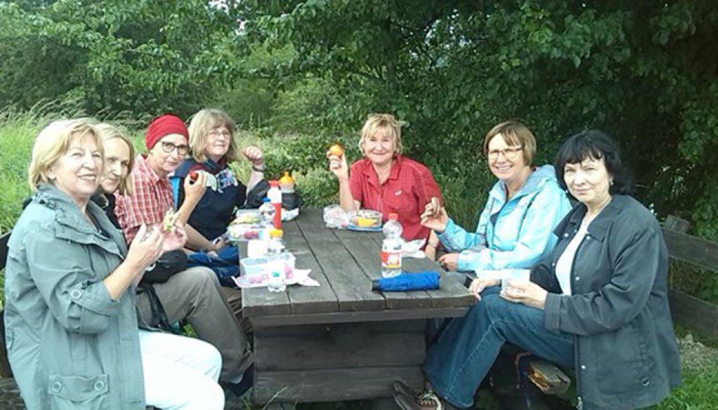 7 Frauen sitzen in der Runde an einem Picknick-Tisch und lächeln in die Kamera © FRIEDA